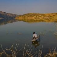 Ein Junge sitzt auf einer Schulbank an der Stelle, wo die alte Stadt Hasankeyf durch den Ilosu-Staudamm überflutet wurde.