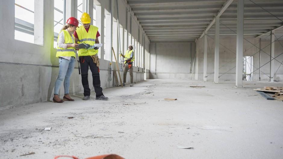 Architekt und Bauarbeiter auf einer Baustelle in München.
