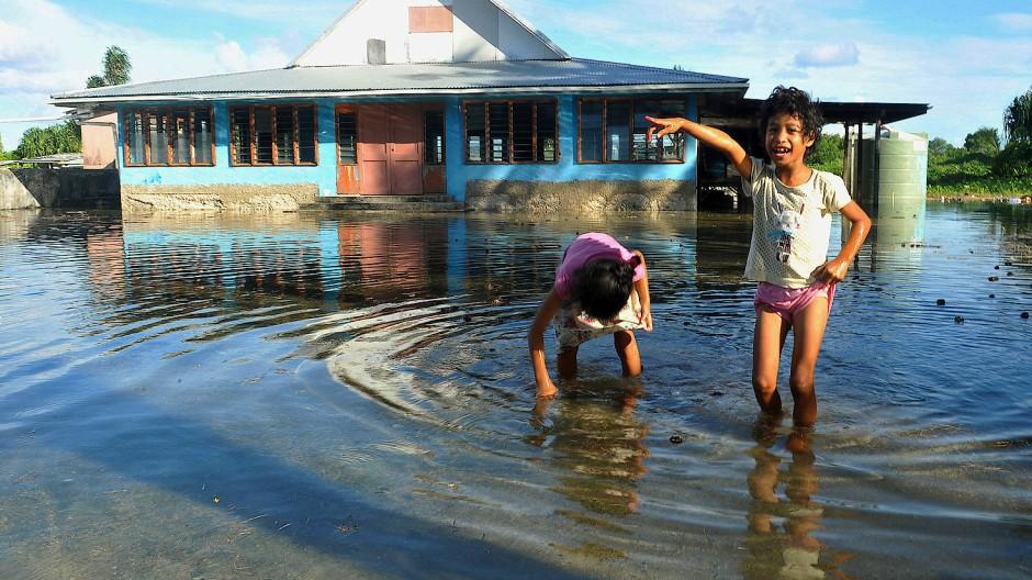 Kinder spielen im Inselstaat Tuvalu im Meer.