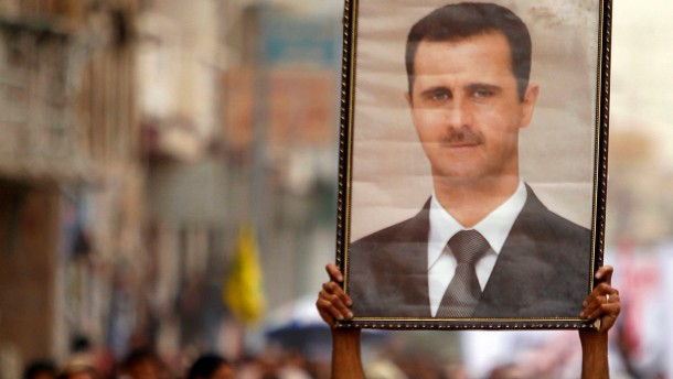 A Shi'ite anti-government protester holds up a poster of Syrian President Bashar al-Assad during a demonstration against Israeli air strikes in Syria, in Sanaa