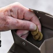 Eine ältere Frau holt Kleingeld aus ihrem Portemonnaie.