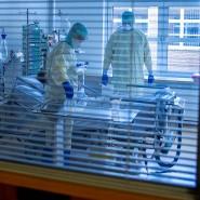 Mediziner und Pfleger versorgen einen an Covid-19 erkrankten Patienten in einem Zimmer des besonders geschützten Teils der Intensivstation des Universitätsklinikums Greifswald.
