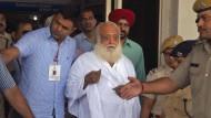 Asaram Bapu wird von Polizisten am Jodhpur Flughafen begleitet.