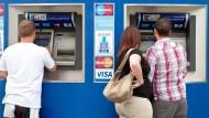 Kunden stehen an Bankautomaten, um Bargeld zu ziehen – und nutzen immer seltener den Service in Bankfilialen.