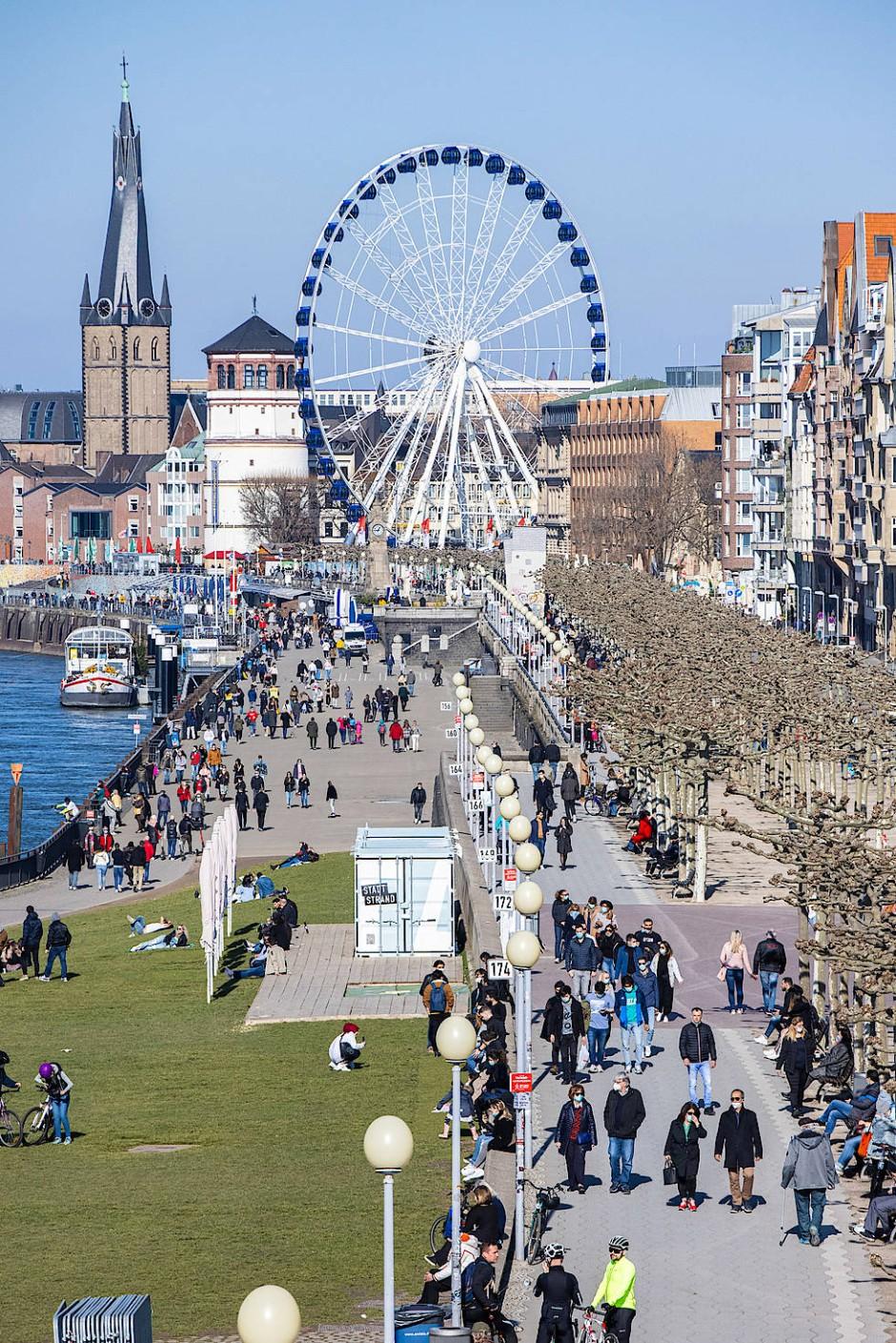 Düsseldorf: Menschen gehen am Sonntag bei Sonnenschein am Rheinufer spazieren