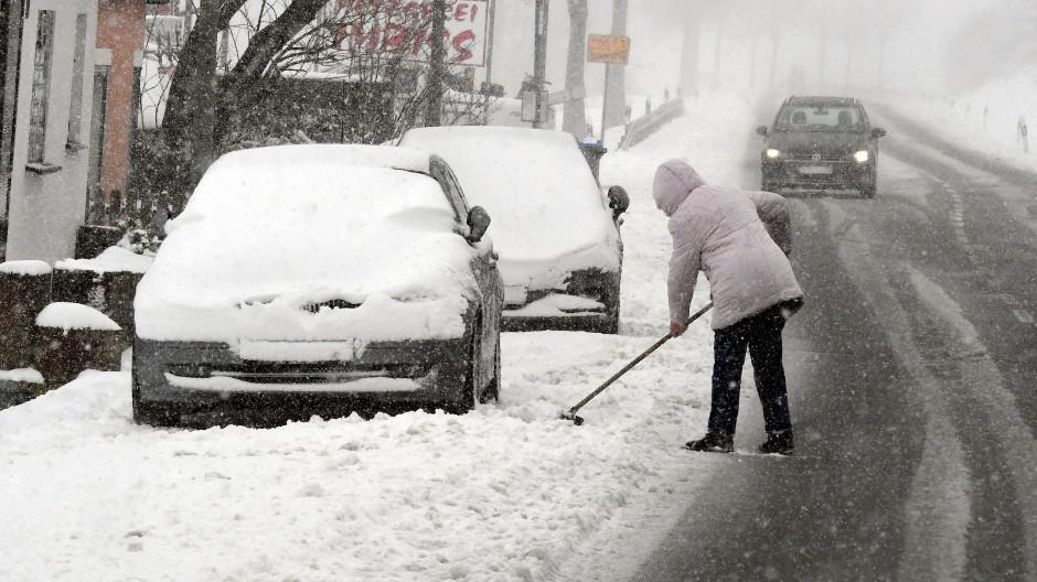 Winterberg in Nordrhein-Westfalen: Eine Frau schippt am Mittwoch auf dem Bürgersteig Schnee.