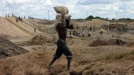 Ein Kongolese balanciert seine Erträge auf dem Rücken durch eine Mine im südlichen Kongo.