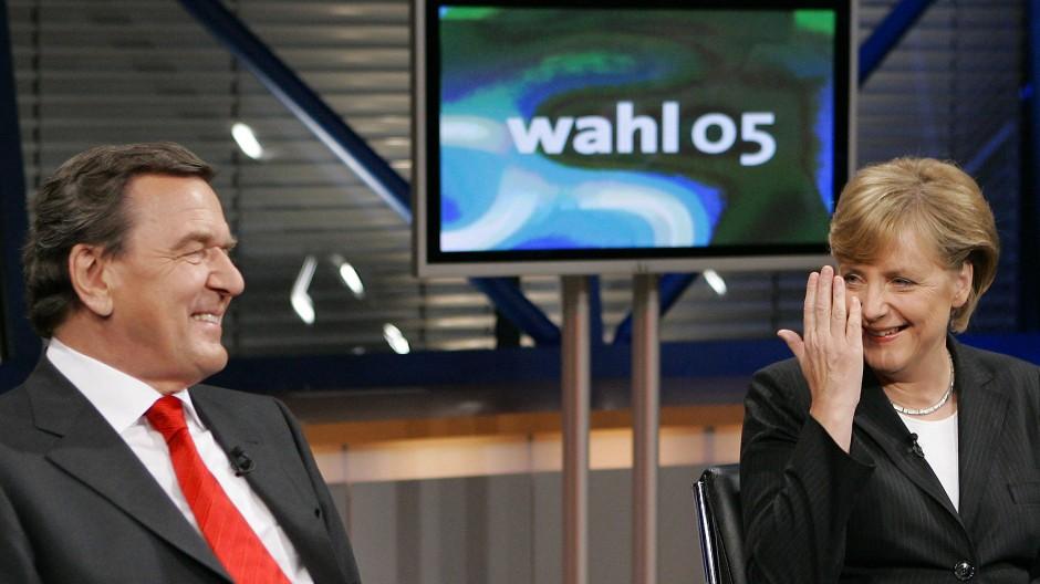 Bundeskanzler Gerhard Schröder und die damalige CDU-Vorsitzende Angela Merkel unterhalten sich am 12. September 2005 in einem Fernsehstudio.