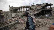 Die Terrorgefahr in Afghanistan reißt nicht ab. Ein afghanischer Polizist läuft an einem explodierten Gebäude vorbei (Archivbild).