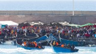 Zwei Boote kommen auf Gran Canaria an, wo sie von anderen Migranten schon erwartet werden.