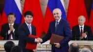 Auf gute Zusammenarbeit: Huawei-Vize Guo Ping und MTS-Chef Alexei Kornya schütteln die Hände, im Hintergrund applaudieren Vladimir Putin und Xi Jinping.