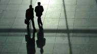 Zwei Männer im Anzug, von denen einer einen Aktenkoffer trägt, werfen lange Schatten.