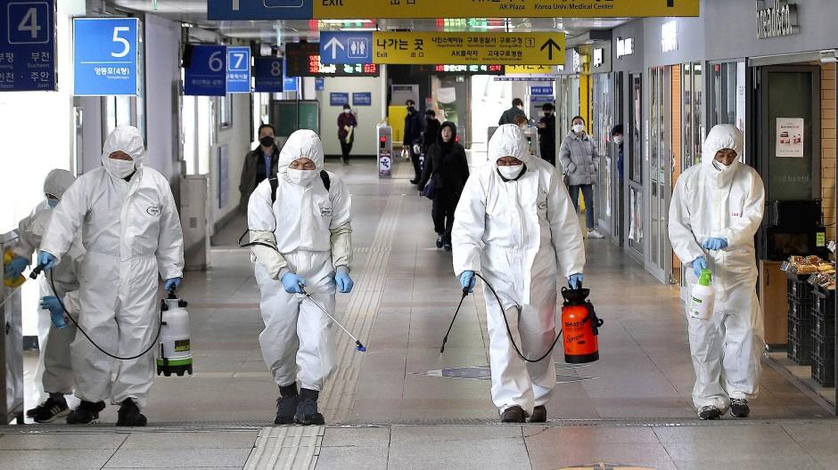 Arbeiter in Schutzanzügen sprühen Desinfektionsmittel in einer U-Bahn-Station in Seoul als Maßnahme gegen die Ausbreitung des Coronavirus.