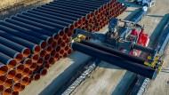 Mit einem Spezialkran werden tonnenschwere Rohre für Nord Stream 2 im Hafen von Sassnitz-Mukran (Mecklenburg-Vorpommern) auf einen Lagerplatz transportiert (Archivbild).