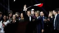Macron mit seiner Familie und Mitarbeitern vor dem Louvre