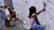 Eine Frau deutet auf das Foto eines 12 Jahre alten Mädchens, das nach dem Brand noch vermisst wird – so wie viele andere.