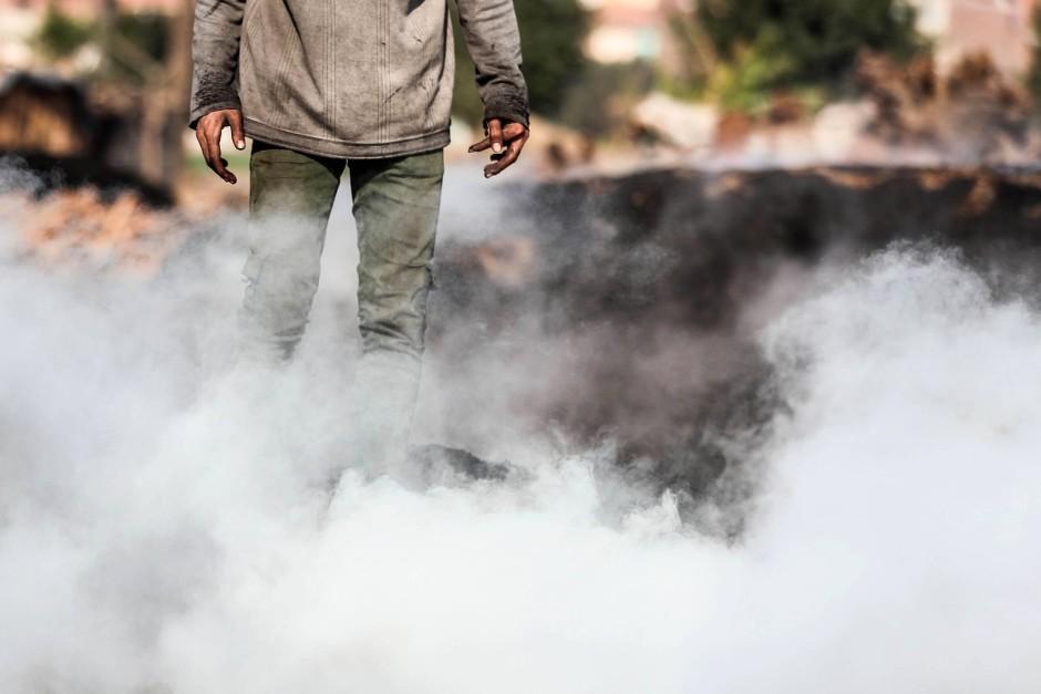 Ein ägyptischer Arbeiter steht im Rauch einer Kohle-Fabrik, die im nördlich von Kairo im fruchtbaren Nil-Delta liegt.
