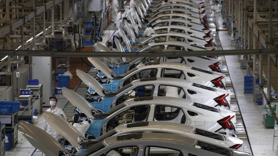 China, Wuhan: Arbeiter in der Fabrik von Dongfeng Honda Automobile Co. arbeiten am Fließband.