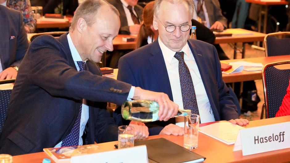 Friedrich Merz schenkt dem Ministerpräsidenten von Sachsen-Anhalt Reiner Haseloff auf dem Parteitag in Magdeburg Wasser ein.
