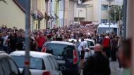 Menschen gehen in einem Trauerzug durch die Innenstadt von Köthen.