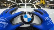 Made in Germany: Mitarbeiter montiert BMW-Emblem im Werk in Dingolfing auf den Kofferraumdeckel.