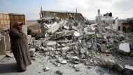 Die Mutter eines palästinensischen Attentäters steht in den Trümmern ihres Hauses in Deir Abu Maschal.