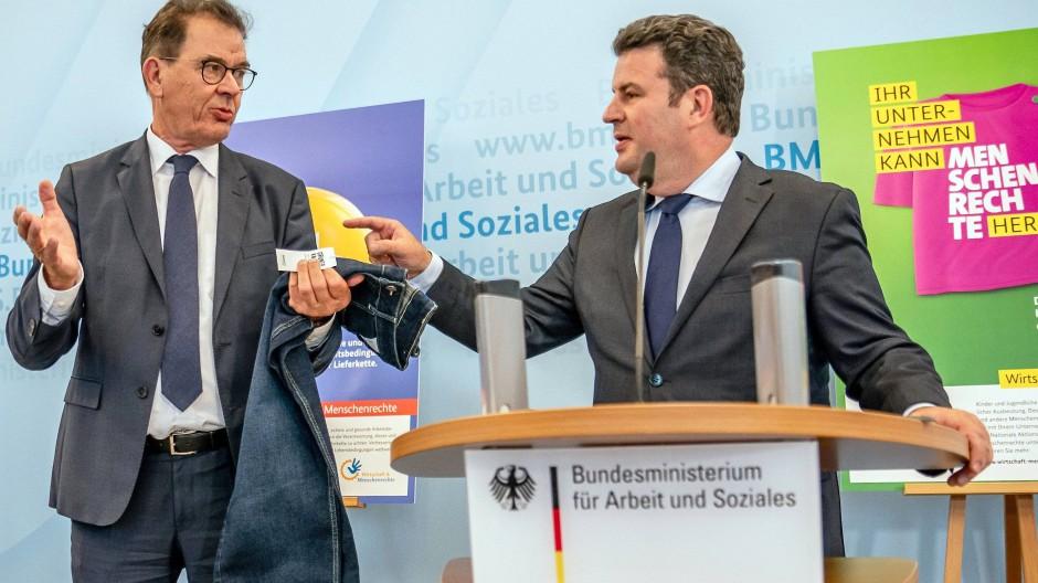 Gerd Müller (CSU, l), Bundesminister für wirtschaftliche Zusammenarbeit und Entwicklung, zeigt neben Hubertus Heil (SPD), Bundesminister für Arbeit und Soziales, eine Jeans, die unter Einhaltung der Menschenrechte hergestellt wurde und nach Angaben von Müller in der Herstellung lediglich zwei Euro teurer ist, auf der Pressekonferenz zum Lieferkettengesetz am 14. Juli 2020