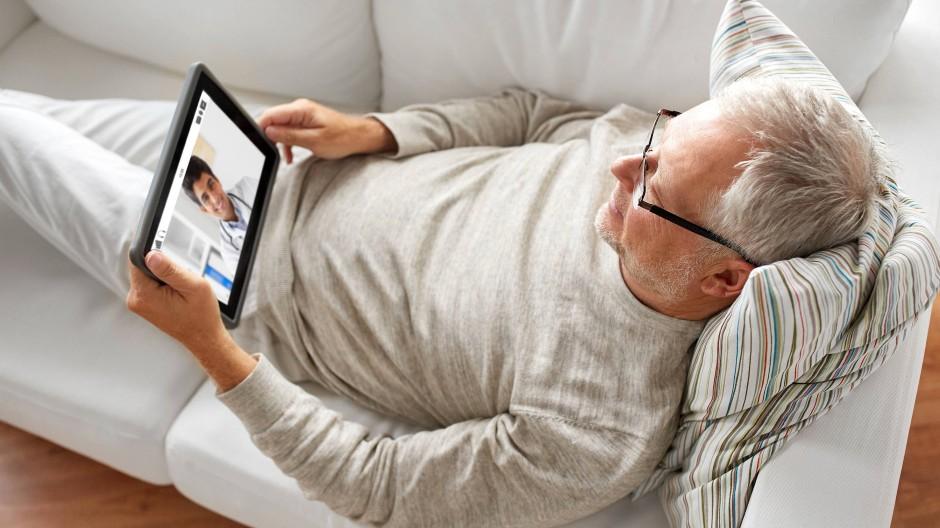 Ein älterer Mann sitzt mit seinem Tablet auf dem Sofa.