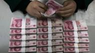 Ein Bankangestellter zählt Yuan-Noten.