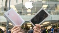 Umsatz mit iPhones: Eine Frau hält in München neu gekaufte iPhones in die Luft.