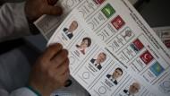 Ein Wahlhelfer verteilt Stimmzettel, auf dem Kandidaten für die Präsidentenwahl aufgelistet sind.