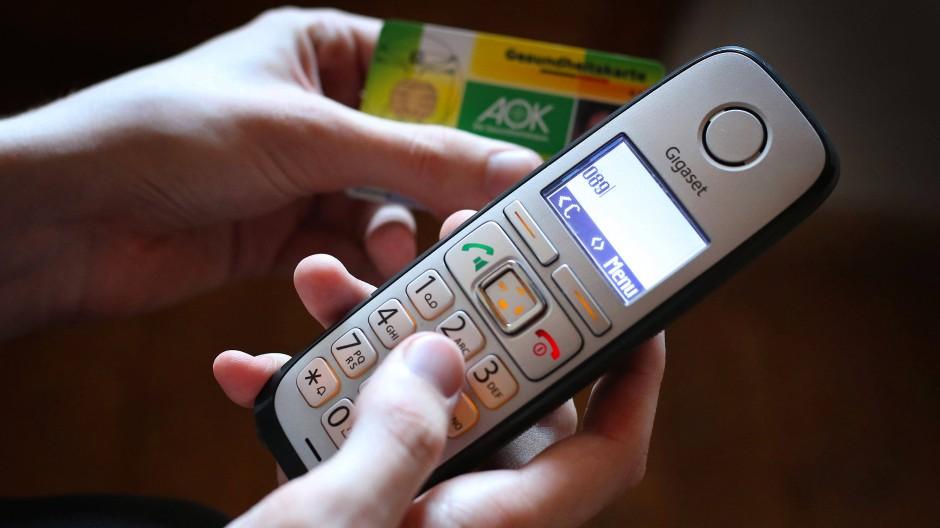 Ein Mann hält eine Gesundheitskarte der Allgemeinen Ortskrankenkasse (AOK) in der Hand, während er am Telefon eine Nummer wählt.