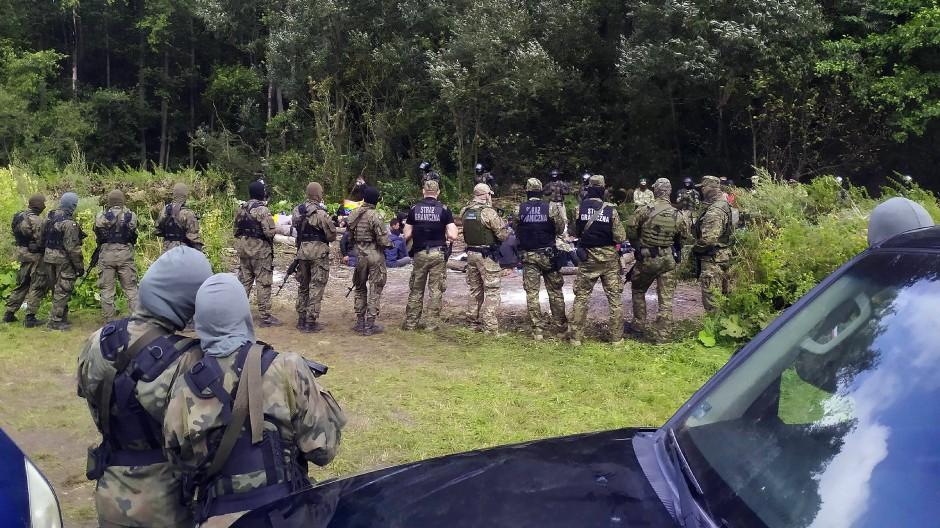 Migranten und polnische Grenzbeamte im Dorf Usnarz Gorny am 19. August