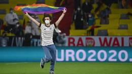 Störer flitzt während Hymne mit Regenbogen-Flagge über den Platz