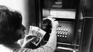 Automat der ersten Stunde: Eine Frau hebt im Jahr 1969 Geld in Köln ab.