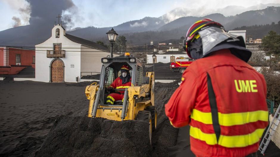 La Palma: Einsatzkräfte des Militärs entfernen schwarze Asche vom Vulkan, der hinter einer Kirche auf der Kanareninsel La Palma weiter Lava ausstößt.