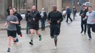 Wer ist schneller? Facebook-Gründer Mark Zuckerberg (links) läuft 2016 mit Bodyguards durch Berlin.