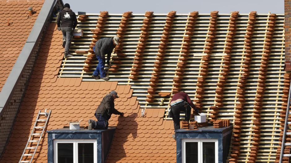Dachdecker decken ein Haus mit neuen Ziegeln.