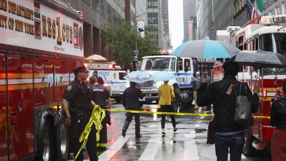 Ein Polizist hält ein Absperrband, um Passanten von dem Unglücksort eines Hubschraubers fernzuhalten.
