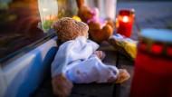 Zwei Stofftiere und Kerzen liegen als Erinnerung an die verstorbene Dreijährige vor dem Eingang ihrer Kindertagesstätte.