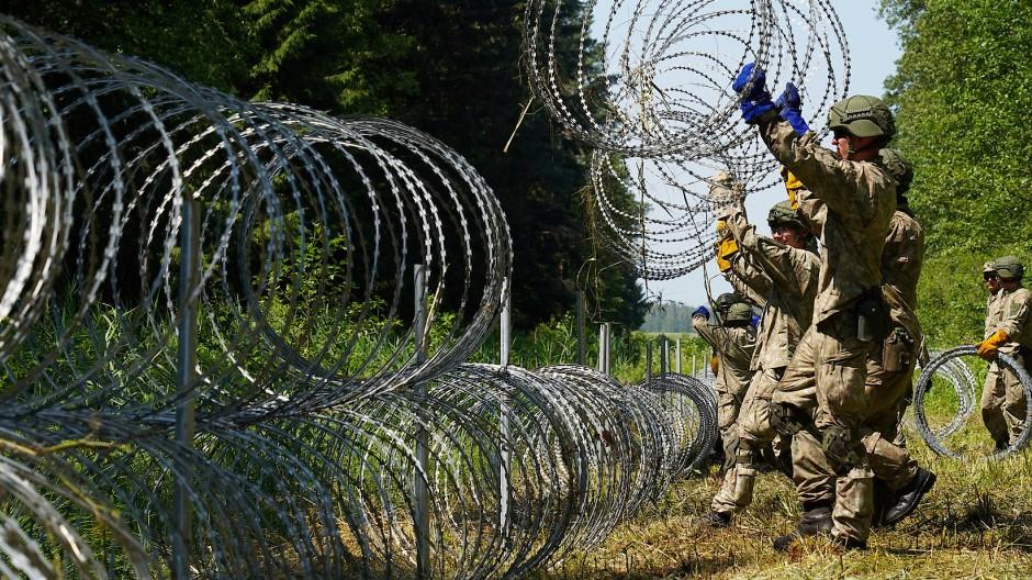 Litauische Soldaten errichten wegen der vielen illegalen Grenzübertritte am 9. Juli einen Zaun an der Grenze zu Belarus.