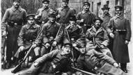 Eine Gruppe bewaffneter Arbeiter und Soldaten in Kiel im November 1918 für einen Fotografen.