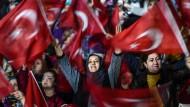 Bei einer Demonstration in Istanbul schwenken diese Unterstützerinnen von Präsident Erdogan türkische Fahnen.