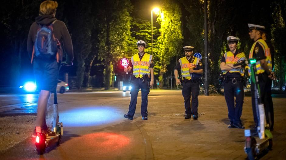 Die Münchner Polizei kontrolliert einen E-Tretroller-Fahrer.