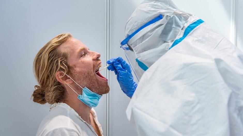 Im Corona-Testzentrum vom Deutschen Roten Kreuz am Franfurter Flughafen lässt ein Mann, der aus Nicaragua zurückgekommen ist, einen Abstrich für einen Corona-Test nehmen.