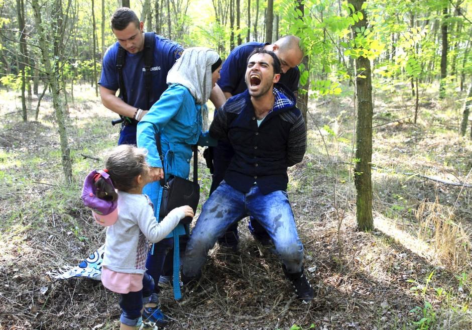 Ungarische Polizisten nehmen an der Grenze zu Serbien eine syrische Familie fest.