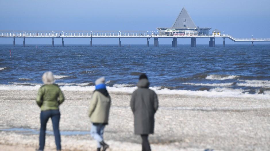 Spaziergänger sind am Samstag am Strand von Ahlbeck auf der Insel Usedom unterwegs.