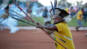 A native Brazilian aims an arrow at riot police during a demonstration in Brasilia