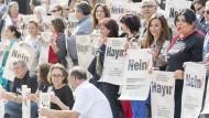 """Mitglieder der """"Nein""""-Initiative in Hessen demonstrieren mit Schildern in Frankfurt."""