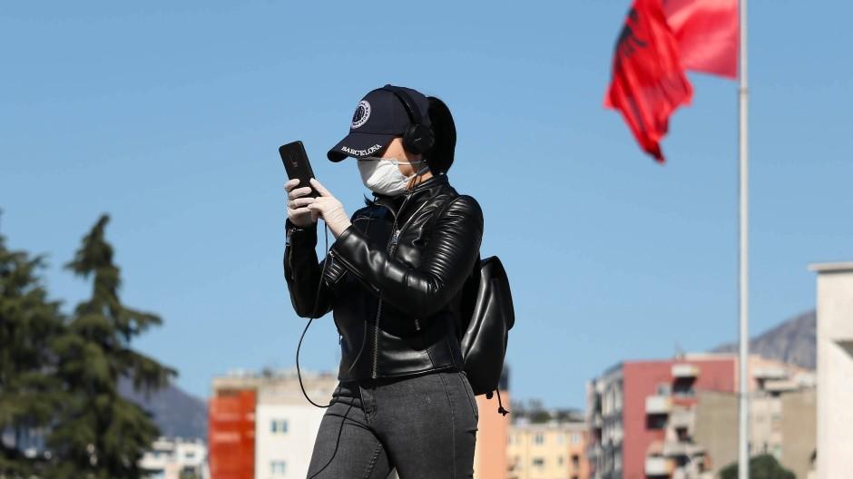 Eine Frau in Tirana konsultiert ihr Smartphone